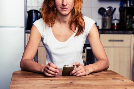 Young redhead woman sitting in kitchen with her phone Stock Photo - 21923920