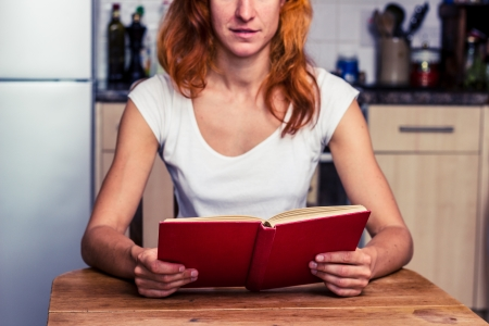 Young redhead woman sitting in kitchen and reading Stock Photo - 21923921