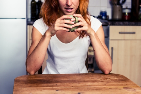 Young woman is drinking coffee in her kitchen Stock Photo - 21923924