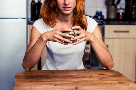 Young woman is drinking coffee in her kitchen Stock Photo - 21923925