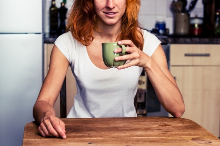 Young woman is drinking coffee in her kitchen Stock Photo - 21923926