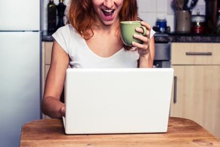 젊은 여자가 그녀의 부엌에서 커피를 마시고 노트북에 노력 스톡 콘텐츠