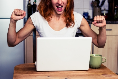 Young woman is very excited about something on her laptop Stock Photo - 21923930