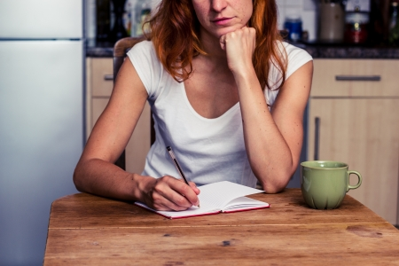 Young woman sititng in kitchen is trying to write Stock Photo