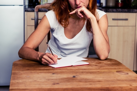 shopping list: Young woman trying to write at her kitchen table Stock Photo