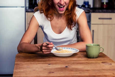 Young woman having breakfast in her kitchen photo