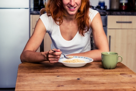 Young woman having cereal for breakfast in her kitchen photo