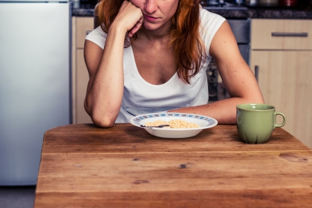 persona deprimida: La mujer joven est� cansada de que los cereales para el desayuno de nuevo Foto de archivo