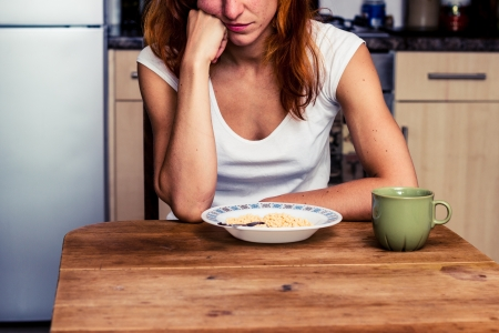 Young woman is tired of having cereal for breakfast again photo