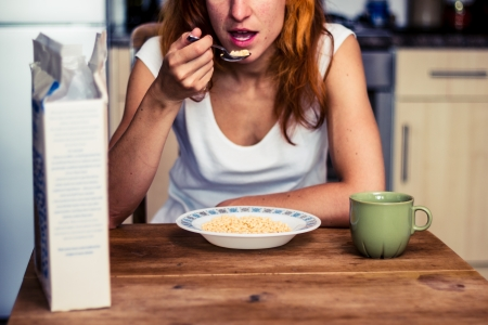 Young woman eating breakfast in her kitchen photo