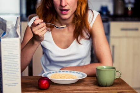 Young woman eating cereal and fruit for breakfast in her kitchen photo