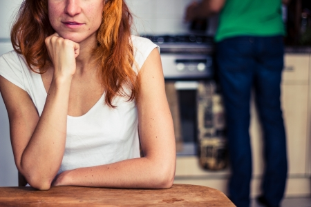 Young woman in kitchen thinking while man is cooking in background Stock Photo - 21924115