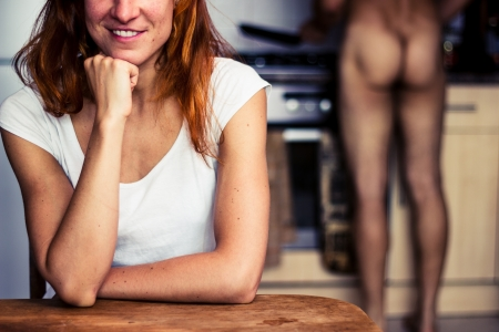 Happy young woman waiting for naked husband to cook for her Stock Photo - 21924118