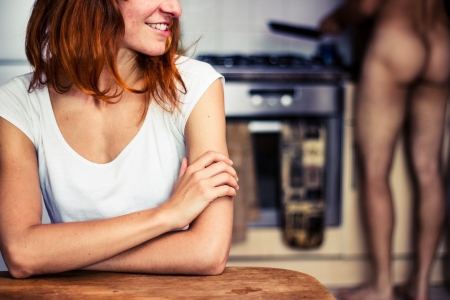 Happy young woman waiting for naked boyfriend to cook for her Stock Photo - 21924119