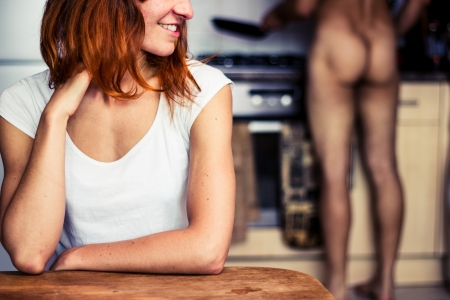 Happy young woman waiting for naked patner to cook for her Stock Photo - 21924120