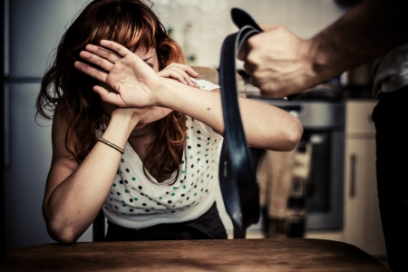 defenceless: Young woman covering her face as she is subjected to domestic violence Stock Photo