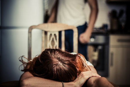 Crying woman at table with abusive husband in background Stock Photo - 21924165
