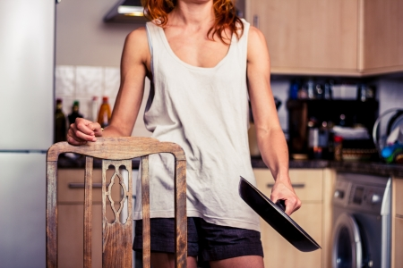 Young woman is standing in kitchen with frying pan photo