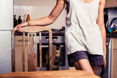 Young woman standing in kitchen holding a chair photo