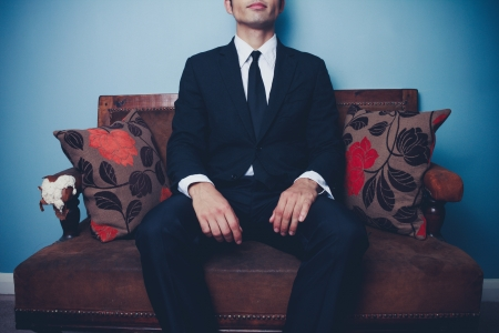 Young businessman is relaxing on vintage sofa photo
