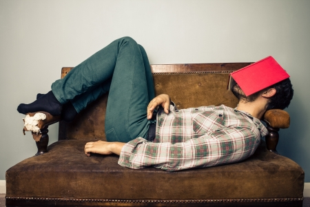 Young man is sleeping on old sofa with book covering his face photo