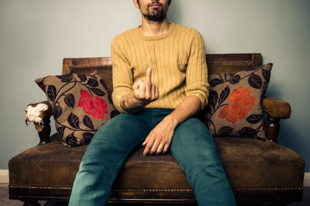 obscene: Young man on sofa displaying obscene gesture Stock Photo