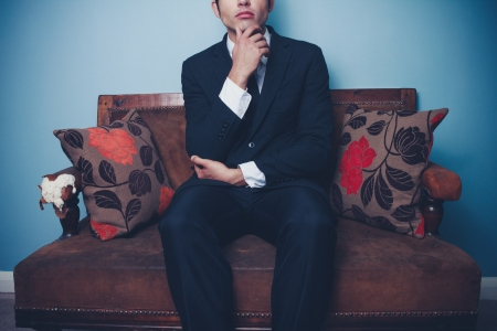 Young businessman on vintage sofa is thinking photo