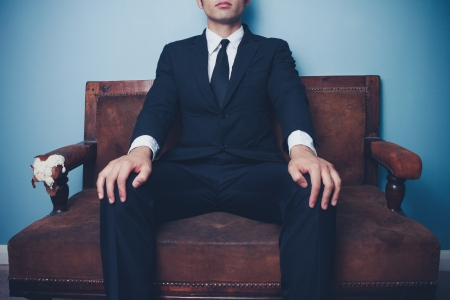 Young businessman is sitting on sofa in a powerful pose Stock Photo - 21994653