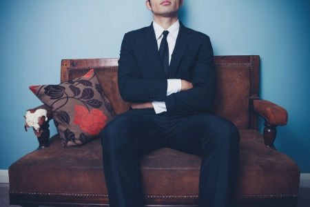 Young businessman is sitting on sofa with his arms crossed