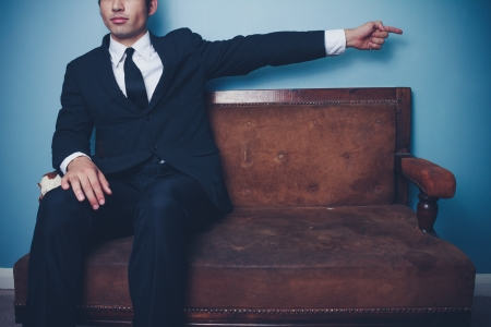 Young businessman on sofa is pointing right photo