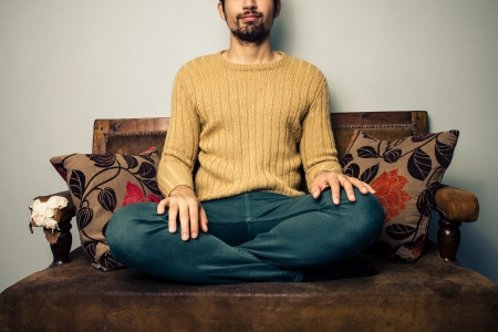 speculating: Young man relaxing on old vintage sofa Stock Photo