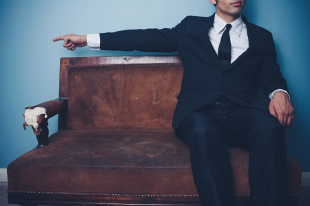 Young businesman on sofa pointing left Stock Photo - 21994663