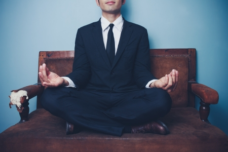 Young businessman sitting on vintage sofa and meditating photo