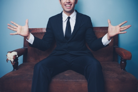 stretched out: Excited young businessman on sofa ggesturing with his hands Stock Photo