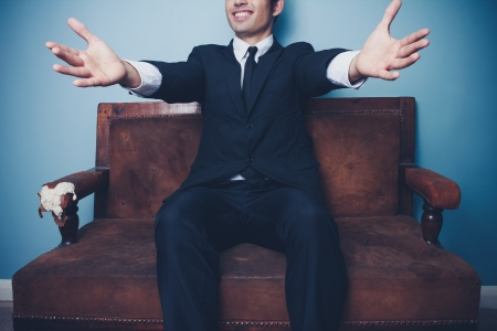 Happy businessman with open arms sitting on sofa photo