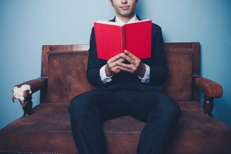 Young businessman is sitting on a sofa and reading a red book photo