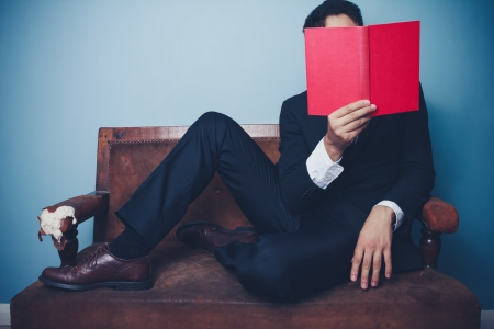 unrecognisable people: Young businessman is sitting on a sofa and reading a red book