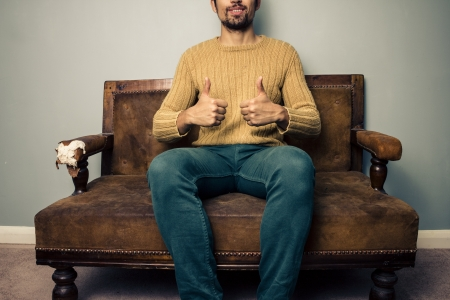 Young man on vintage sofa is giving thumbs up photo