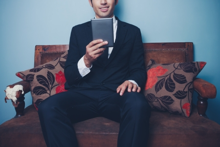 Young businessman is sitting on a sofa and reading on a digital tablet photo