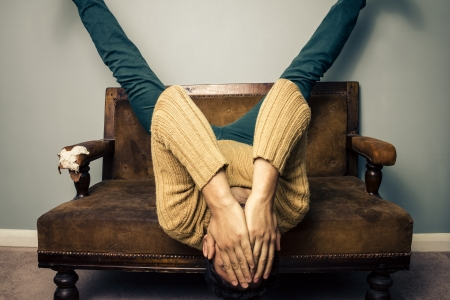 Young frustrated man on vintage sofa is lying upside down