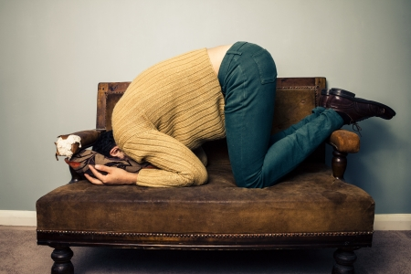 hidden: Young man burrying his face in cushion on vintage sofa