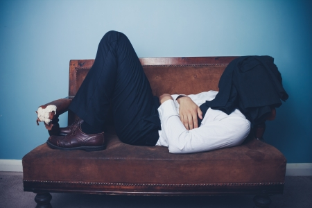 Man in suit is sleeping on sofa with his jacket covering his face photo