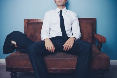 Young businessman is relaxing on a vintage sofa after work photo