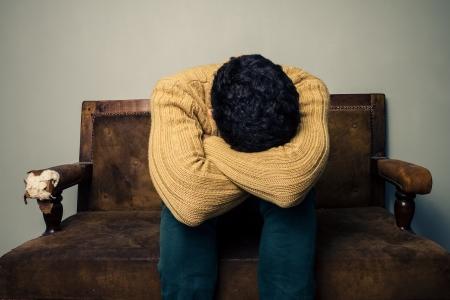 Triste e depresso giovane uomo seduto su un vecchio divano vintage photo