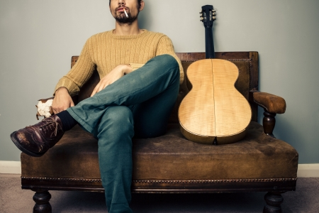crossed cigarette: Stereotypical musician with his guitar is sitting on a sofa and smoking a cigarette