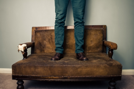bad manners: Man is standing on an old sofa still wearing his shoes Stock Photo