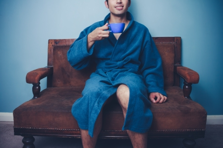 Man in bathrobe is sitting on sofa and drinking coffee photo