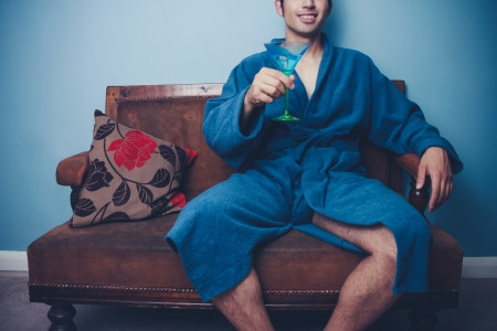 Succesful young man in dressing gown drinking a cocktail Stock Photo - 22141138