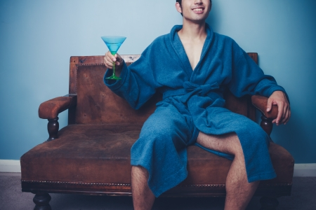 jetset: Succesful young man in dressing gown drinking a cocktail