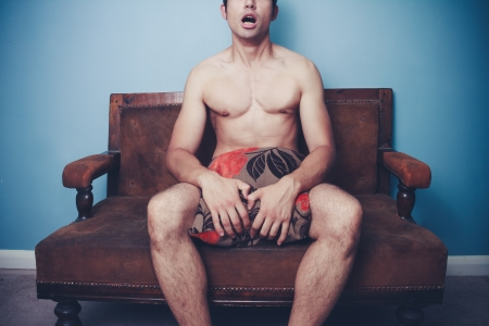 Young naked man sitting on sofa and covering himself with a cushion photo
